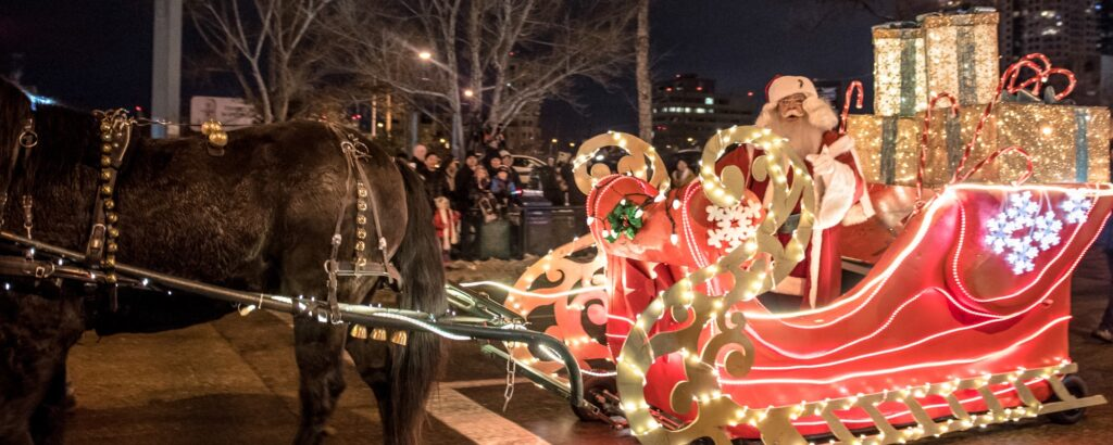Santa's illuminated sleigh being pulled by reindeer. Source: http://asian.ca/heritagemonth/wp-content/uploads/2018/11/Santa-parade.jpg