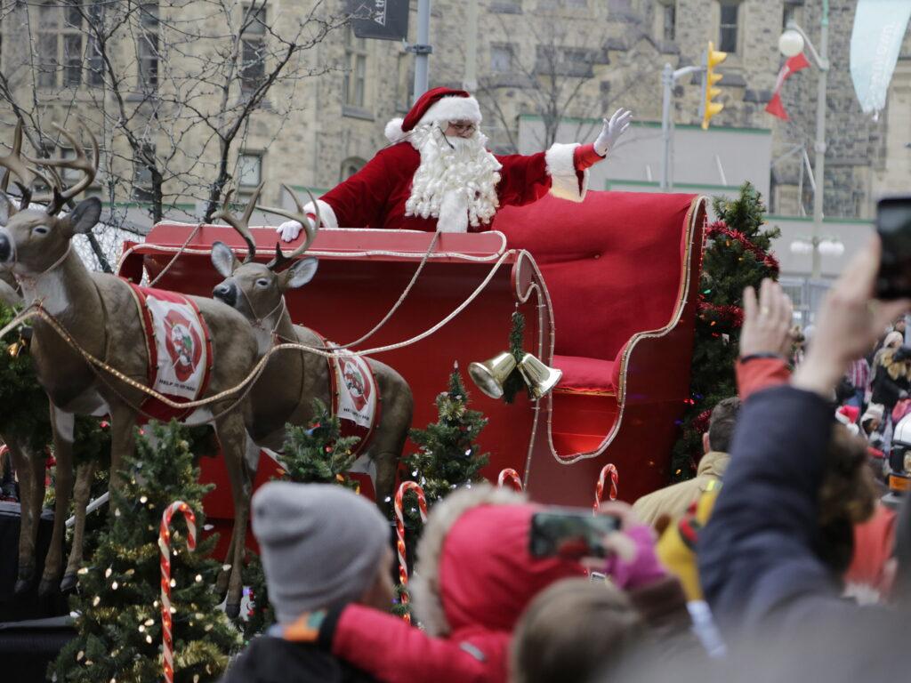 Santa waving to the crowd from his sleigh in Ottawa. Source: https://postmediaottawasun.files.wordpress.com/2017/11/santaparade_012.jpg