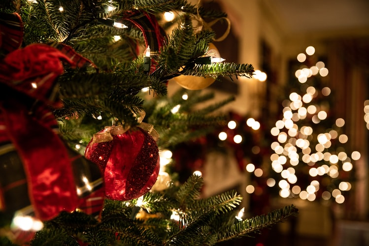 A close-up shot of a Christmas tree with ornaments, with Christmas lights visible in the background.
