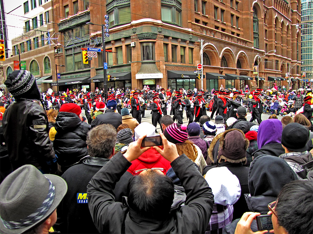 Large crowds of people watching Toronto's Santa Claus Parade. Source: http://www.torontocitylife.com/wp-content/uploads/2010/11/santa-claus-parade-1-1024.jpg